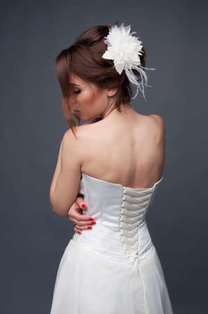 updo: Elegant bride with brown short hair updo and bare shoulders white wedding dress view from the back Stock Photo