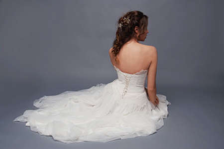 headpiece: Bridal fashion. Brunette bride with pearl headpiece and white wedding gown view from the back sitting in a pile of tulle fabric.