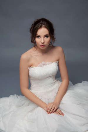 bridal hair: Adorable young bride with brown curly hair sitting in a cloud of tulle. Bridal fashion. Stock Photo