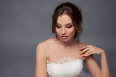 bare shoulders: Adorable young bride with brown curly hair, blue eyes and white dress and bare shoulders