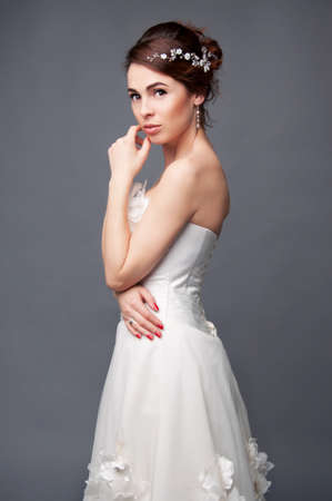 headpiece: Elegant bride with brown short hair updo and bare shoulders white wedding dress and beaded headpiece in her hair