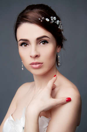 updo: Elegant bride with brown short hair updo and bare shoulders white wedding dress and beaded headpiece in her hair