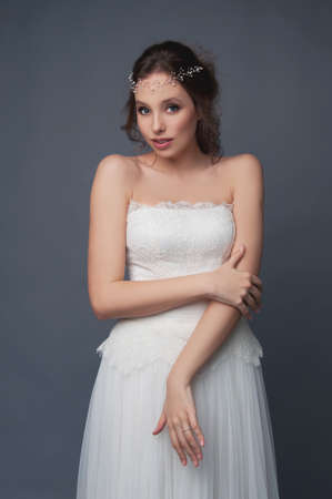 headpiece: Shy cute bride in white wedding dress and beaded headpiece. Bridal fashion. makeup and hairstyle.