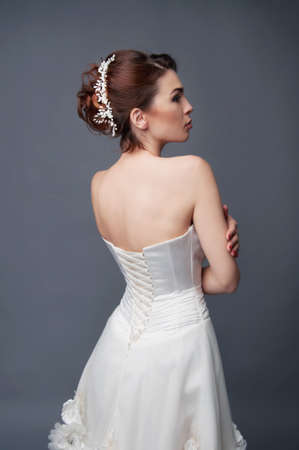 headpiece: Bridal hairstyle. Brunette with curly hair and beaded headpiece. View from the back.