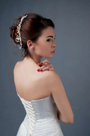 headpiece: Bridal fashion, hairstyle and makeup. Brunette bride in wedding dress and beaded headpiece on gray backdrop.