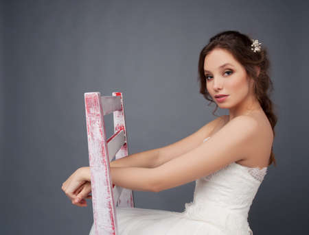 headpiece: Young bride sitting alone on a stool in wedding dress wearing beaded headpiece Stock Photo