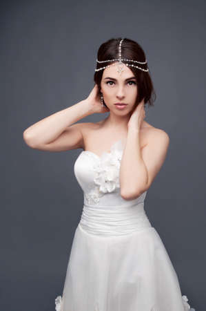bridal makeup: Brunette bride wearing tikka headpiece and white wedding dress. Bridal makeup and fashion.