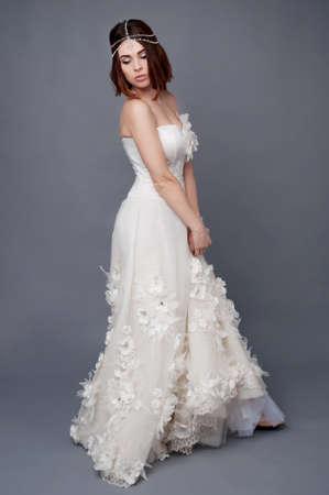 headpiece: Brunette bride wearing tikka headpiece and white wedding dress. Bridal makeup and fashion.