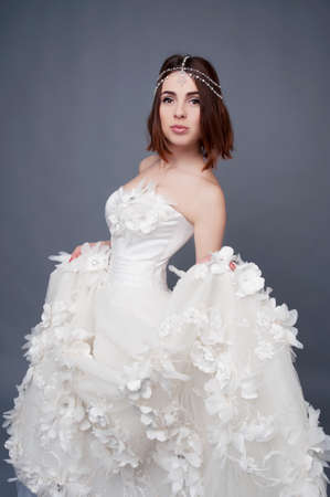 bride dress: Brunette bride wearing tikka headpiece and white wedding dress. Bridal makeup and fashion.