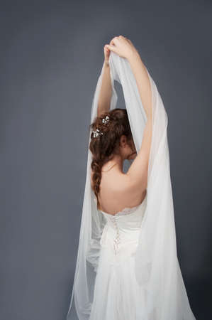 headpiece: Bride in white wedding gown and beaded headpiece posing with veil