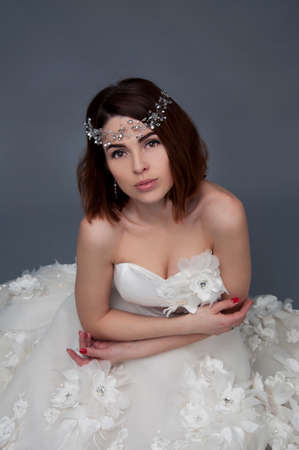 headpiece: Cute woman with brown eyes wearing wedding strapless dress and crystal headpiece