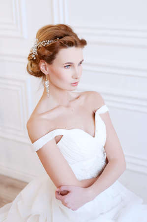 bridal hair: Bridal hairstyle and makeup. Young woman with long blond  hair wearing beaded  headpiece and white lace wedding gown.