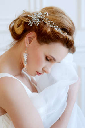 headpiece: Bridal hairstyle and makeup. Young woman with long blond  hair wearing beaded  headpiece and white lace wedding gown.