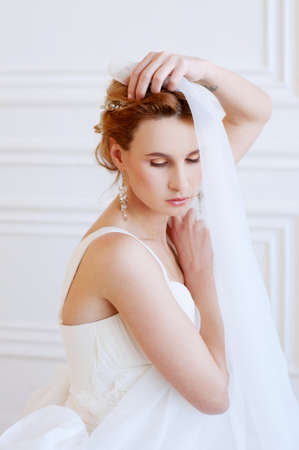 Bridal hairstyle and makeup. Young woman with long blond  hair wearing beaded  headpiece and white lace wedding gown.