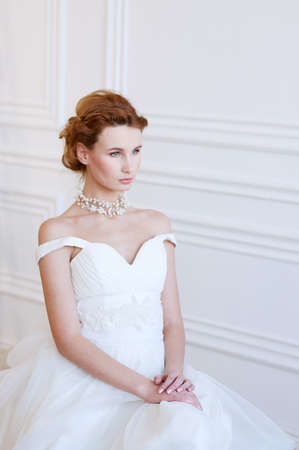 bare shoulders: Young adult caucasian blond bride in white gown wearing light makeup and pearl necklace with bare shoulders. Bridal fashion.