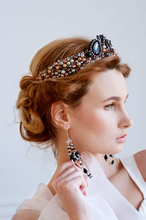 Beautiful royal bride wearing gorgeous dark blue beaded headpiece and earrings