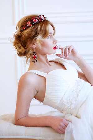 headpiece: Beautiful royal bride wearing gorgeous red beaded headpiece and earrings and red lipstick Stock Photo