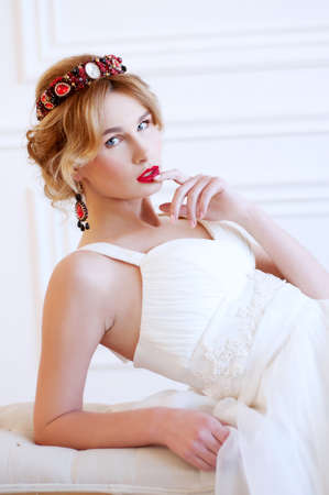 Beautiful royal bride wearing gorgeous red beaded headpiece and earrings and red lipstick Stock Photo