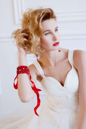 Beautiful blond bride with provocative red lips and red semi precious jewelry
