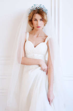 headpiece: Something blue. Blond bride with beaded headpiece wearing white gown and tulle.