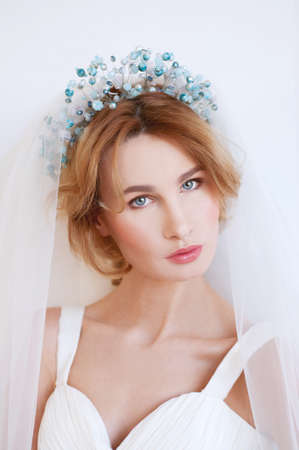 Something blue. Blond bride with beaded headpiece wearing white gown and tulle.