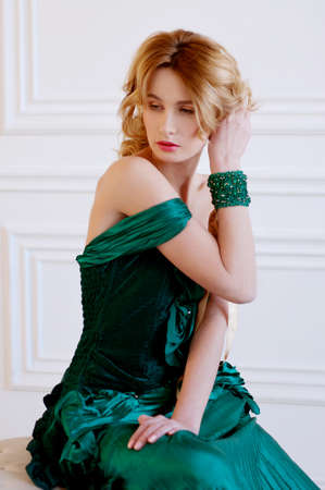 Shapely blond woman in green restoration evening silk gown and beaded bracelet