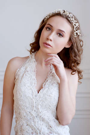 eyes green: Tender young bride with curly brown hair, green eyes, wearing white gown and pearl headpiece