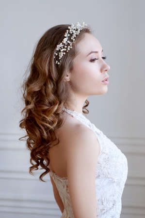 Bridal hairstyle and makeup. Young woman with lonh curly brown hair wearing headpiece and white lace wedding gown. Stock Photo