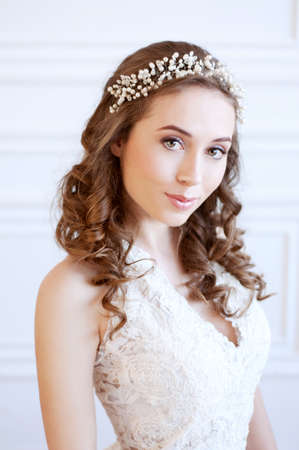 headpiece: Tender young bride with curly brown hair, green eyes, wearing white gown and pearl headpiece