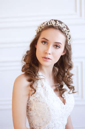 Tender young bride with curly brown hair, green eyes, wearing white gown and pearl headpiece