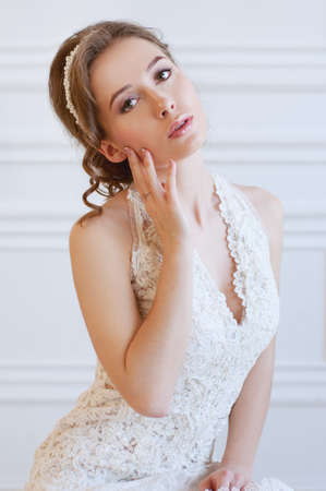 headpiece: Bridal hairstyle and makeup. Young woman with long curly brown hair wearing headpiece and white lace wedding gown. Stock Photo