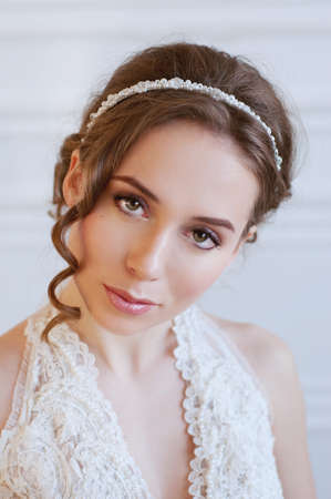 Bridal hairstyle and makeup. Young woman with long curly brown hair wearing headpiece and white lace wedding gown. Stock Photo