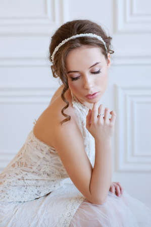headpiece: Bridal fashion. Tender young woman with brown hair and pearl headpiece wearing white gownd and  light pink makeup.