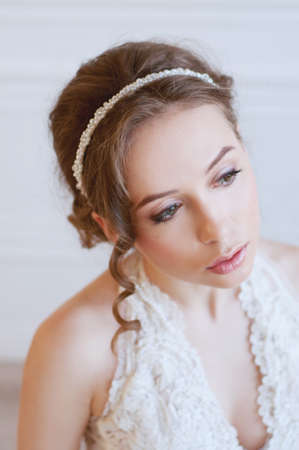 headpiece: Bridal fashion. Tender young woman with brown hair and pearl headpiece wearing white gown and  light pink makeup. Stock Photo