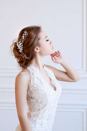 adult mermaid: Young adult caucasian bride demonstrating a white bridal mermaid gown Stock Photo