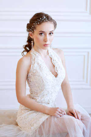 Princess style bride wiyh long brown hair with crystal headpiece and earrigs
