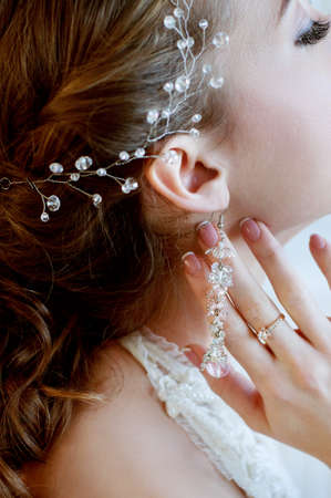 headpiece: Bridal jewelry closeup. Woman wearing engagement ring, earrings and crystal headpiece.