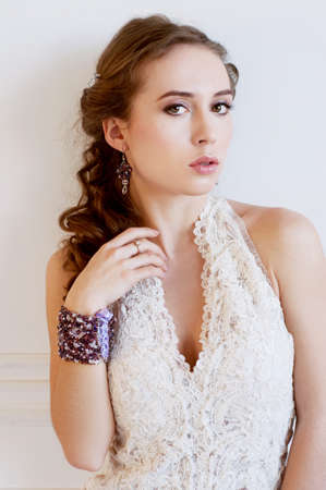 adult mermaid: Tender young bride with curly brown hair, white gown and purple beaded bracelet Stock Photo