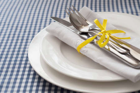 Table setting with blue checkered tablecloth, white napkin and silverware Stock Photo