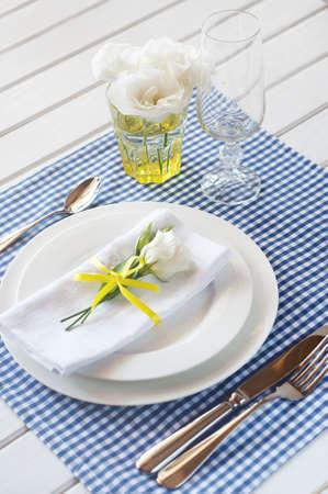 Tischdekoration mit blau karierter Tischdecke, weißer Serviette, Tafelsilber, gelber Verzierung und Blumen