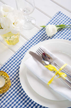 Table setting with blue checkered tablecloth, white napkin, silverware, yellow decoration and flowers