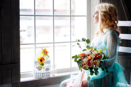 peignoir: Bridal morning boudoir with smiling charming blond woman wearing mint transparent peignoir and holding fresh flowers Stock Photo