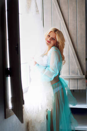 peignoir: Happy bride in turquoise peignoir holding her wedding lace dress Stock Photo