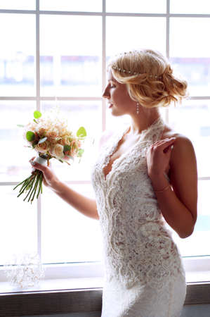 Charming blond bride waiting near the window for her groom wearing white lace dress and pearl headpiece