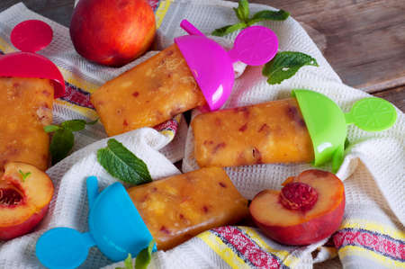 Peach ice lollies with colored sticks on a kitchen napkin with mint leaves Stock Photo
