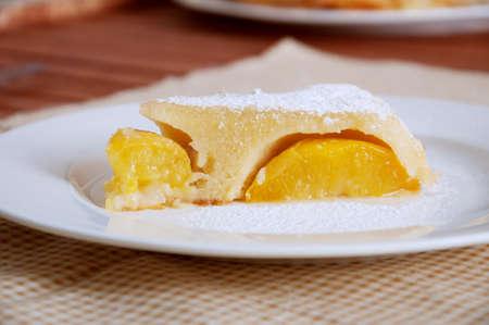 Peach caramel turnover homemade pie sprinkled with sugar powder. Delicious summer dessert. Stock Photo