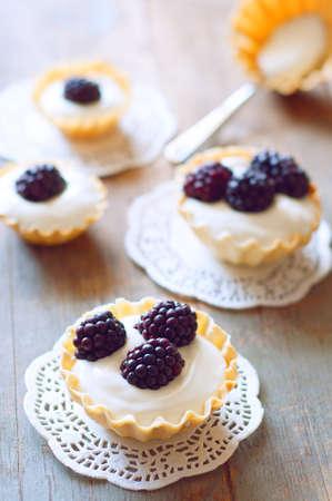 Different size tartlets with cream an fresh dewberries. Sweet berry summer dessert.