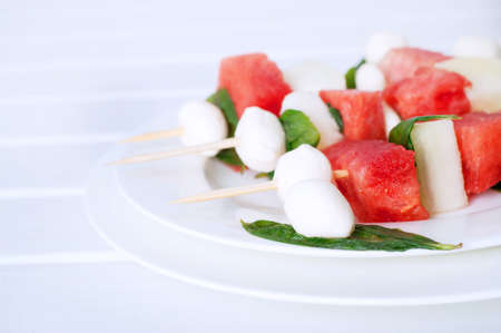 sliced watermelon: Watermelon kebab with spicy sauce, basil and mozzarella cheese. Refreshing summer barbecue snack.