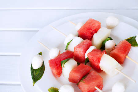 Watermelon kebab with spicy sauce, basil and mozzarella cheese. Refreshing summer barbecue snack.