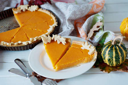 Piece of spicy pumpkin pie cake surrounded by decorative small pumpkins, fallen leaves. Autumn seasonal traditional food.